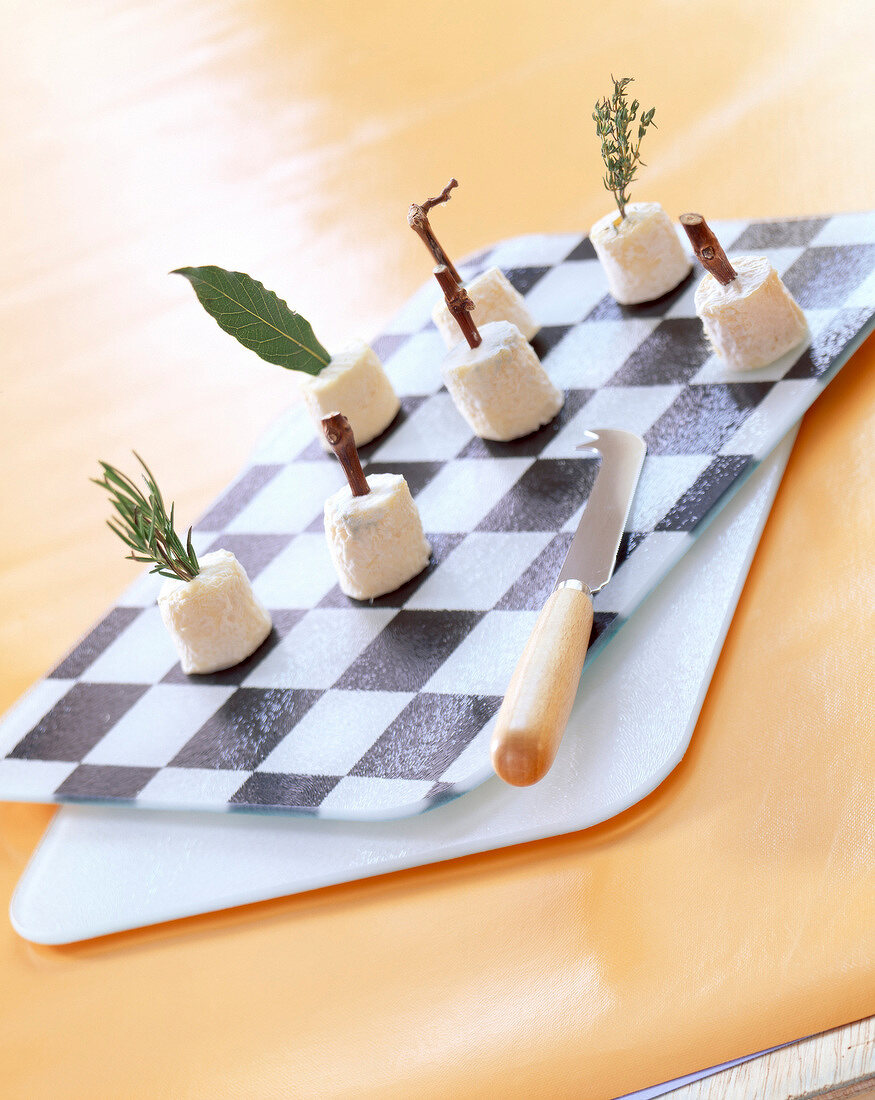 mini goat's cheeses on chessboard cheese platter