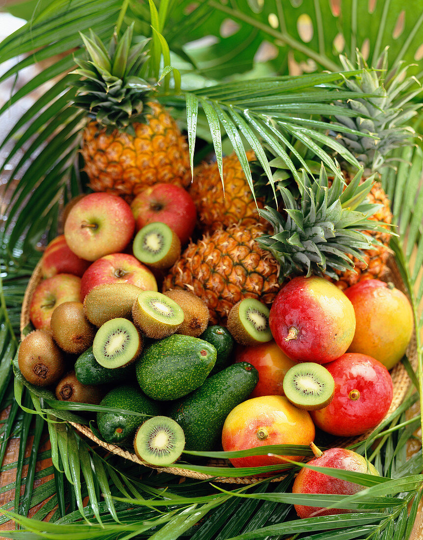 Basket of exotic fruits and leaves