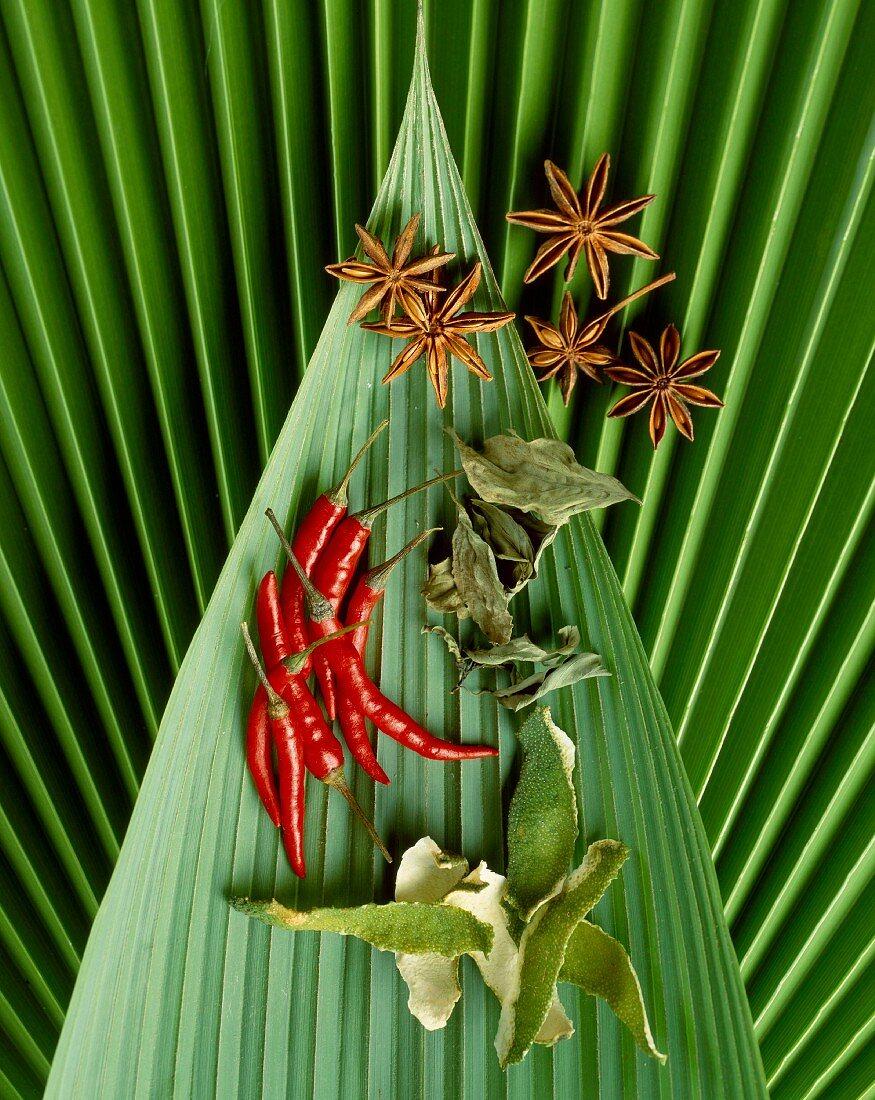 Exotische Gewürze auf Bananenblättern (Chili, Sternanis, Limettenschale, Limettenblätter)