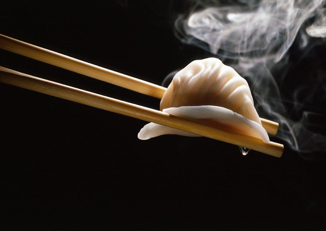 Chinese hakao ravioli on chopsticks