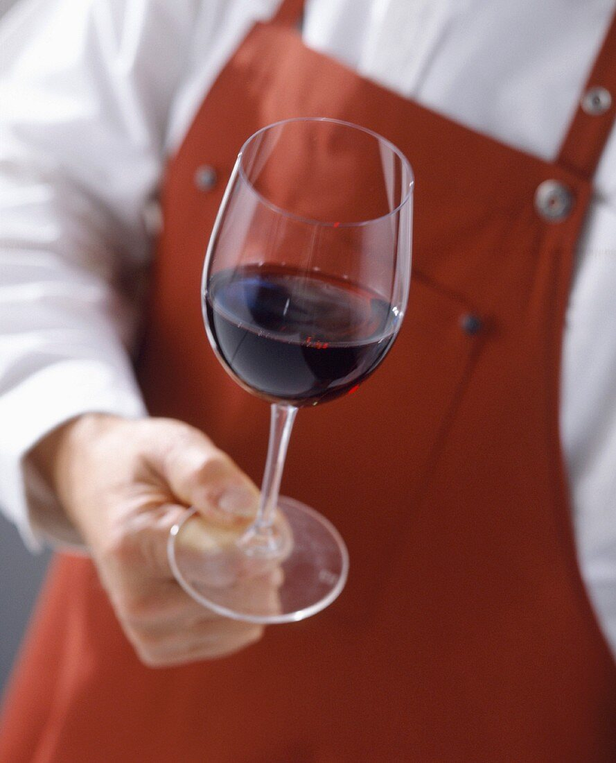 Cellarman with glass of red wine and apron