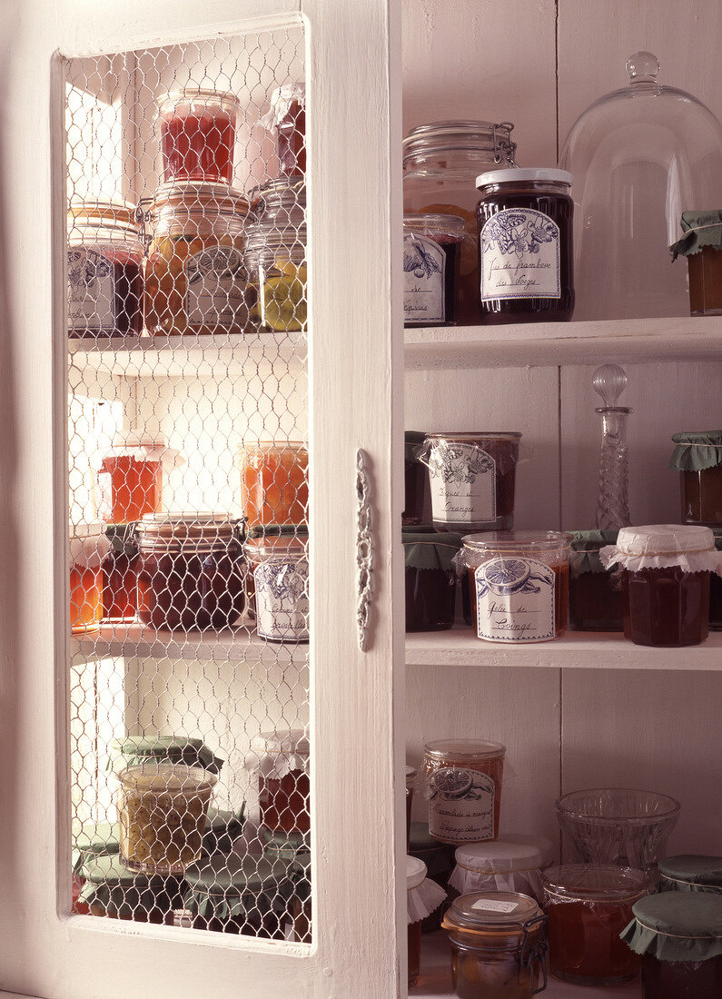 Pots of peach and raspberry jam in cupboard