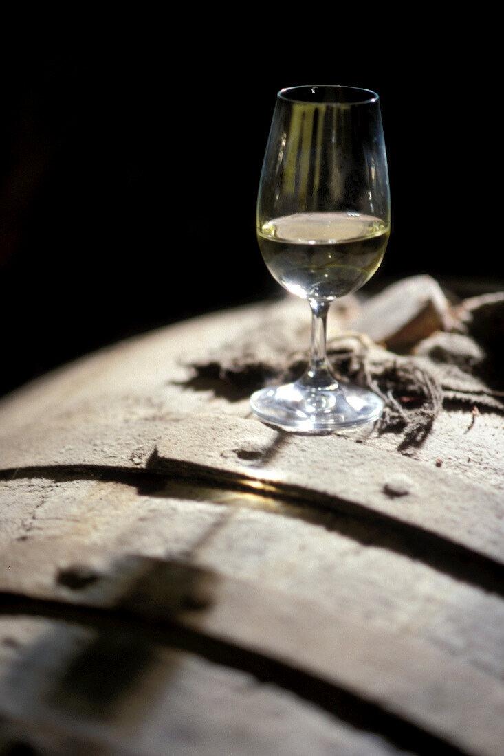 Glass of white wine on barrel