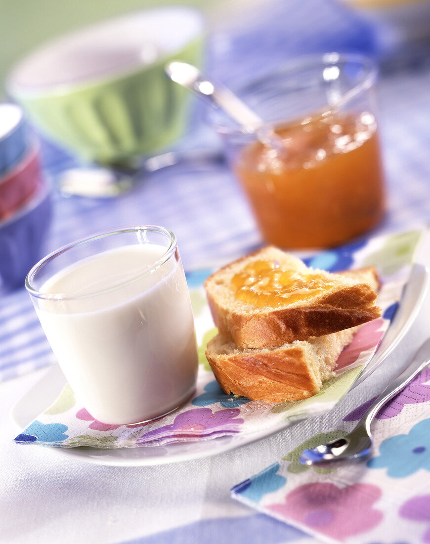 Breakfast with glass of milk, bread and apricot jam