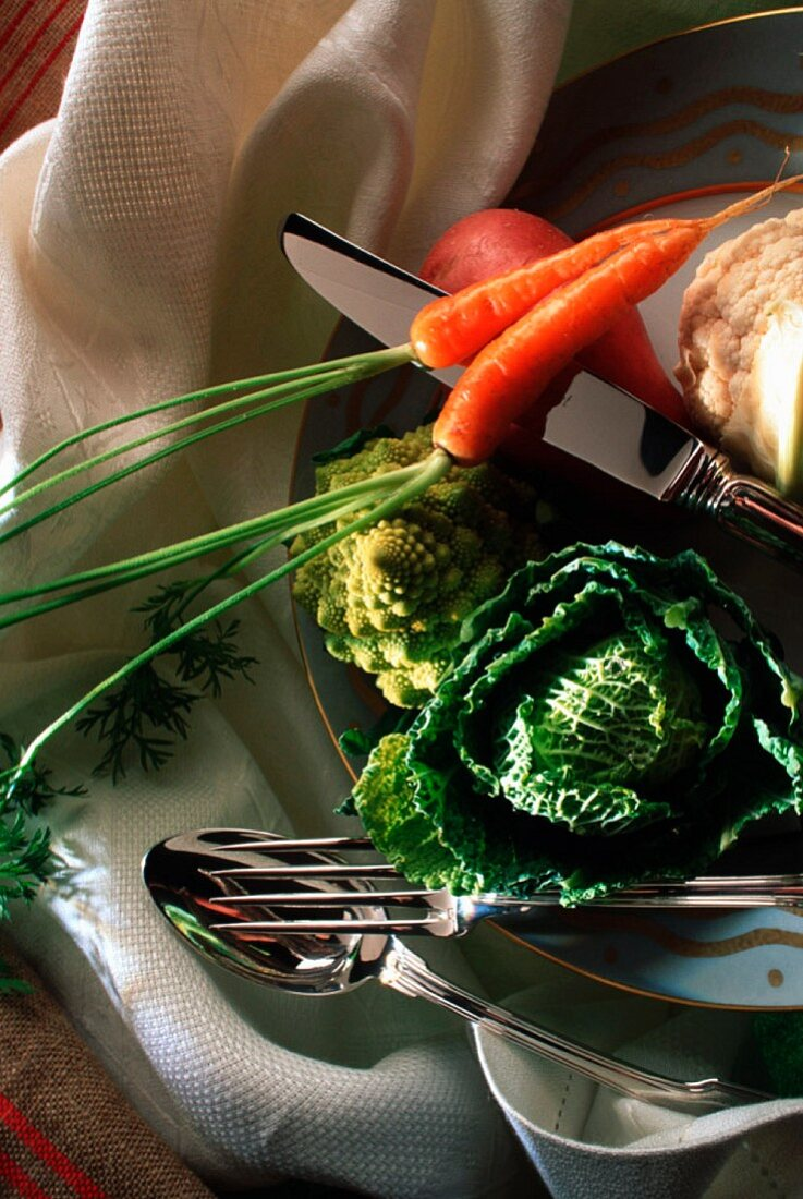 An arrangement of vegetables and silver cutlery