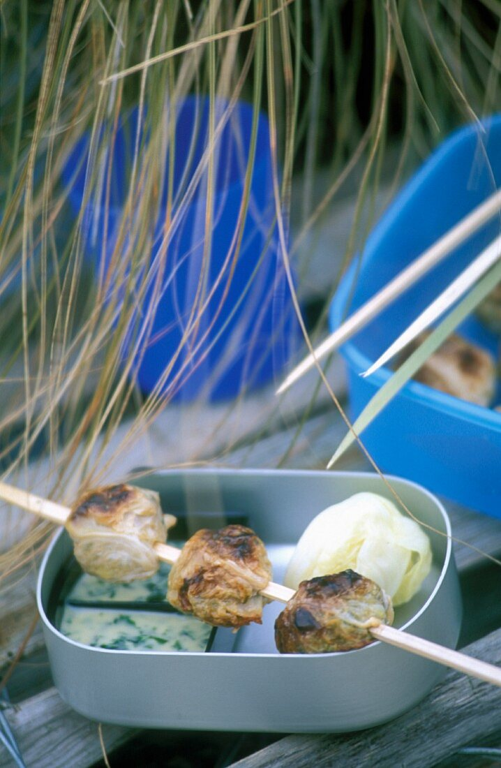 Pastry rolls filled with chicken on skewers on a picnic bowl