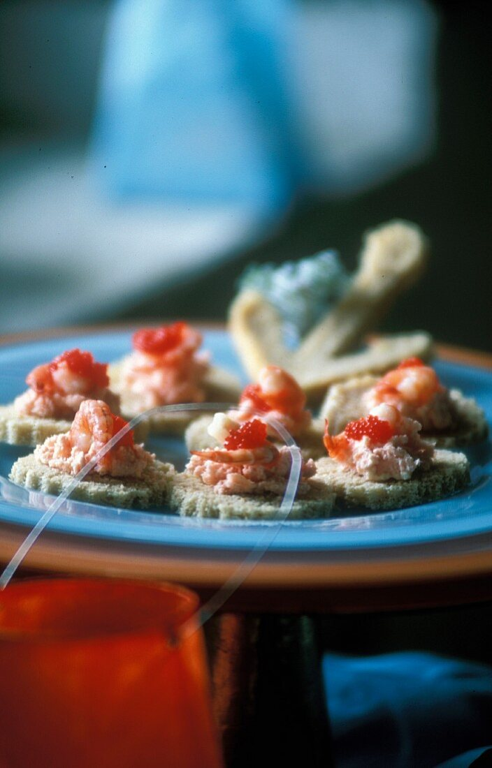 Mini toast topped with crab, shrimp and caviar as an appetiser