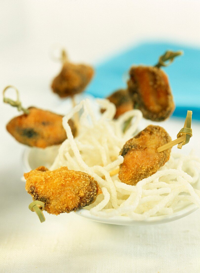 Mussel brochettes stuffed with olives,breaded and fried tapas-style