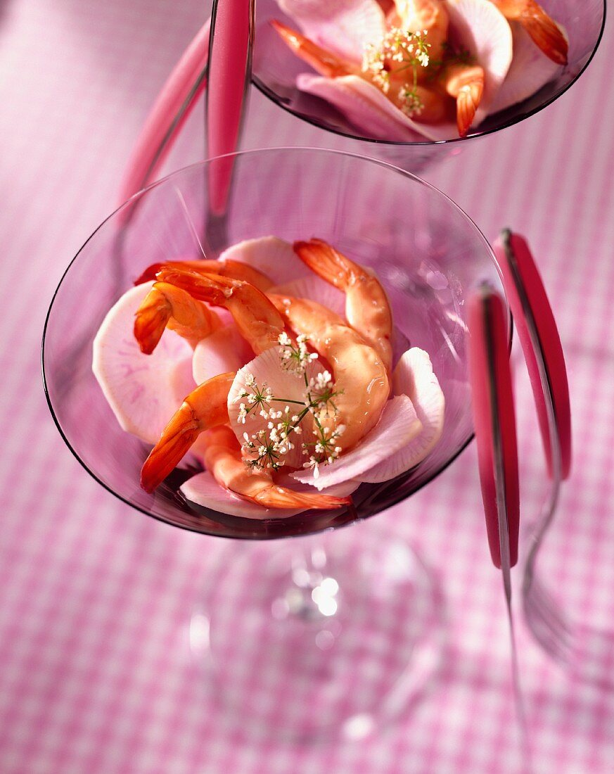 Prawns and radish slices in cocktail glasses