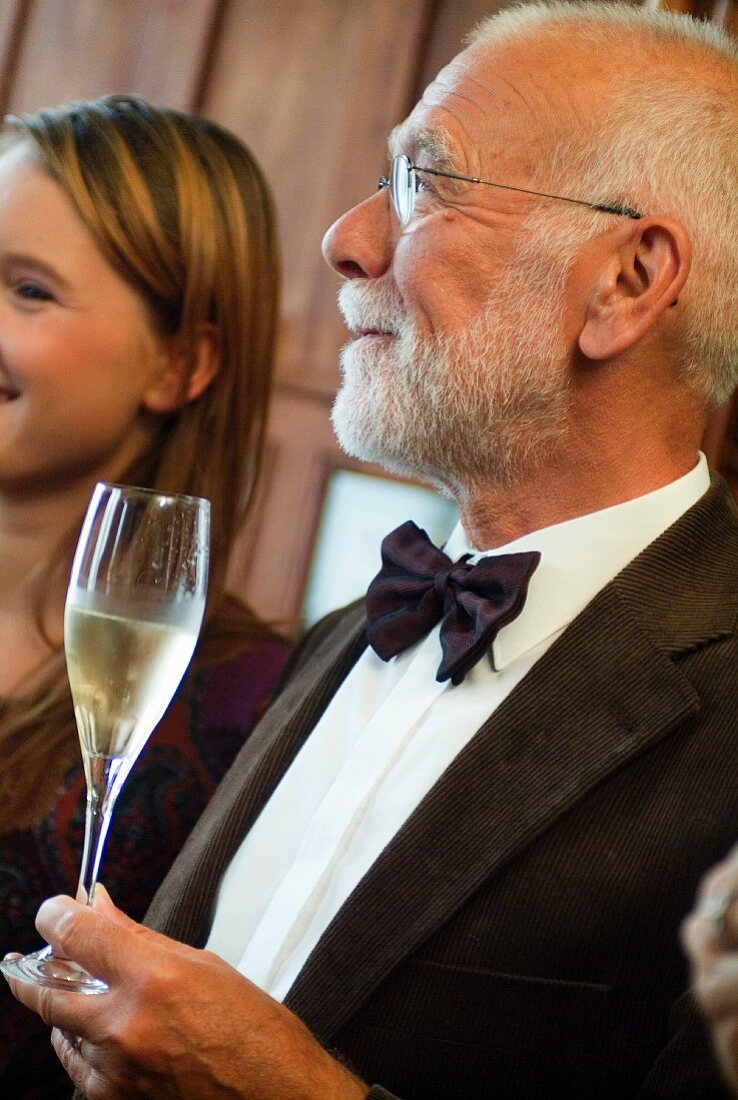 Älterer Mann hält ein Glas Champagner