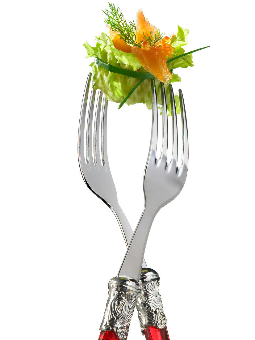 Two forks with lettuce and salmon
