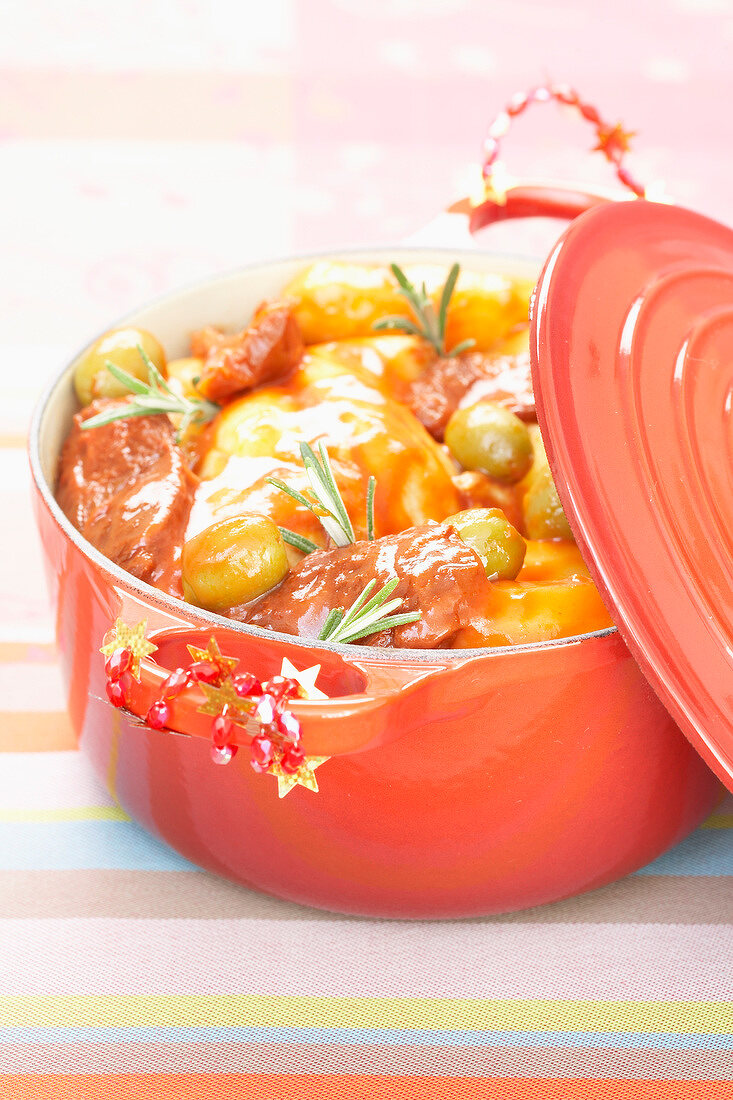 Casserole dish of rabbit legs with tomato sauce and green olives