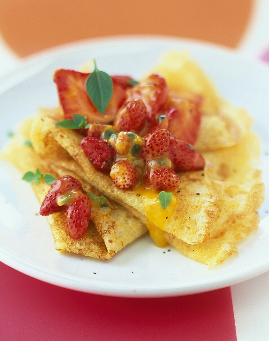 Vanilla-flavored pancakes with pan-fried wild strawberries and passionfruit juice
