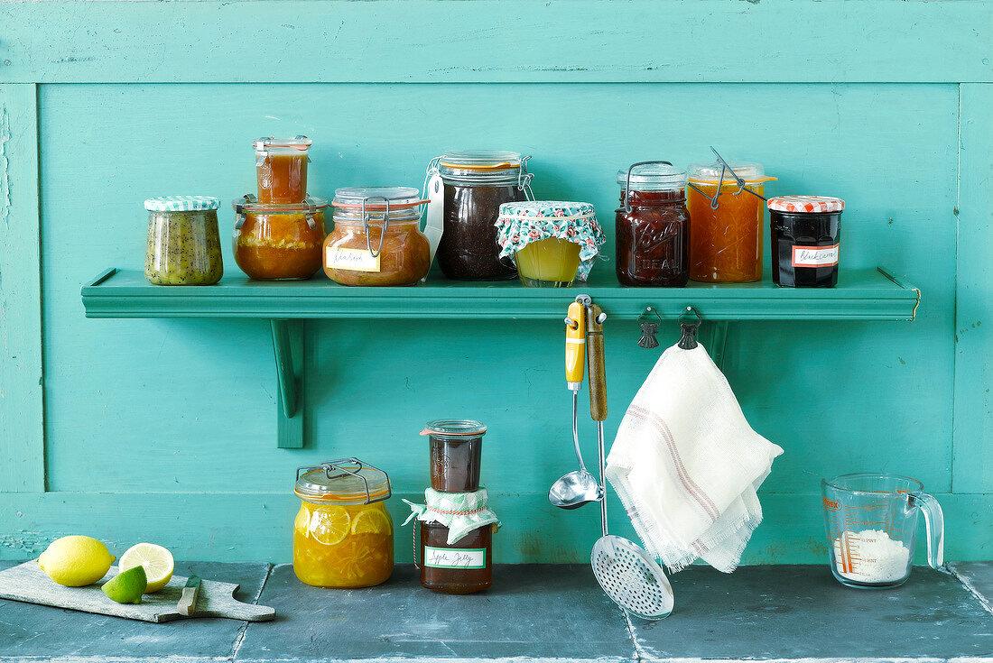 Verschiedene Marmeladengläser auf türkisem Küchenregal
