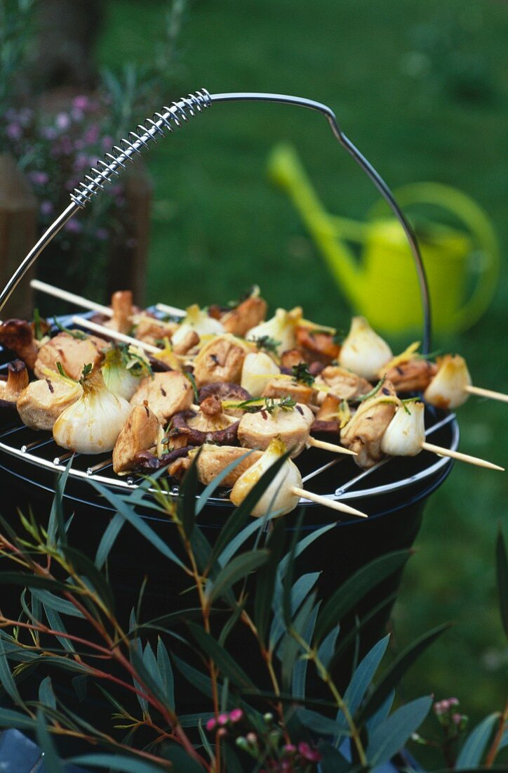 Veal,chicken,spring onion,shiitake and fresh thyme brochettes on the barbecue