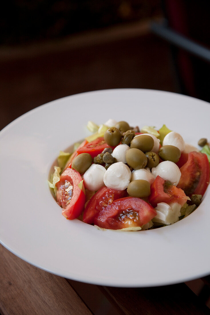 Tomato, mozzarella ball, olive and caper salad