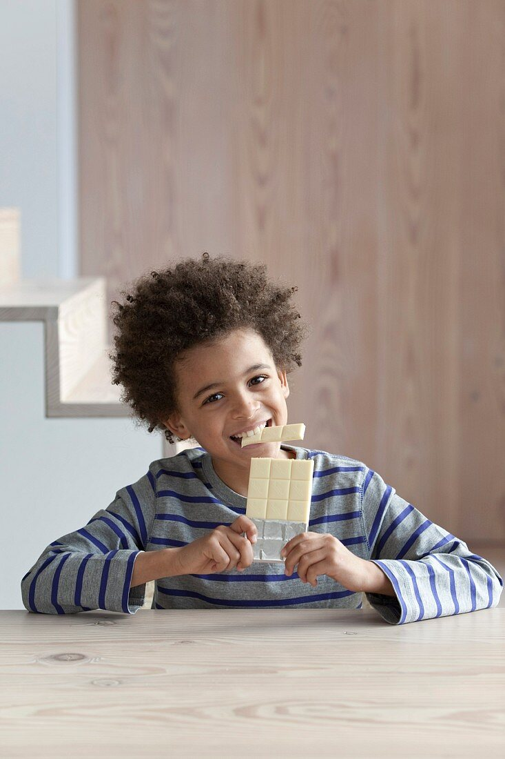 Boy eating a bar of white chocolate