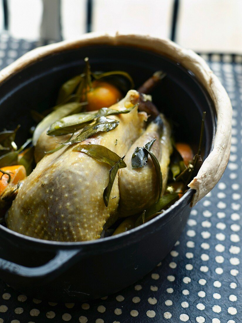 Free-range guinea-fowl with clementines cooked in a casserole dish sealed with pastry