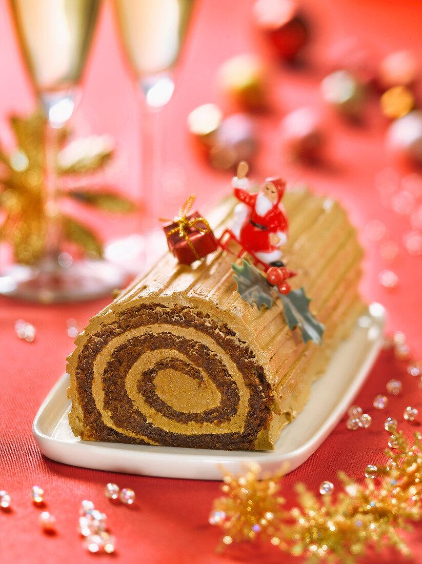 Christmas coffee log cake decorated with Santa Claus