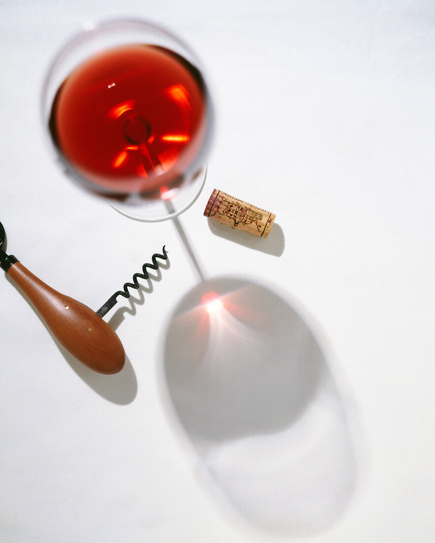 Glass of red wine,corkscrew and cork