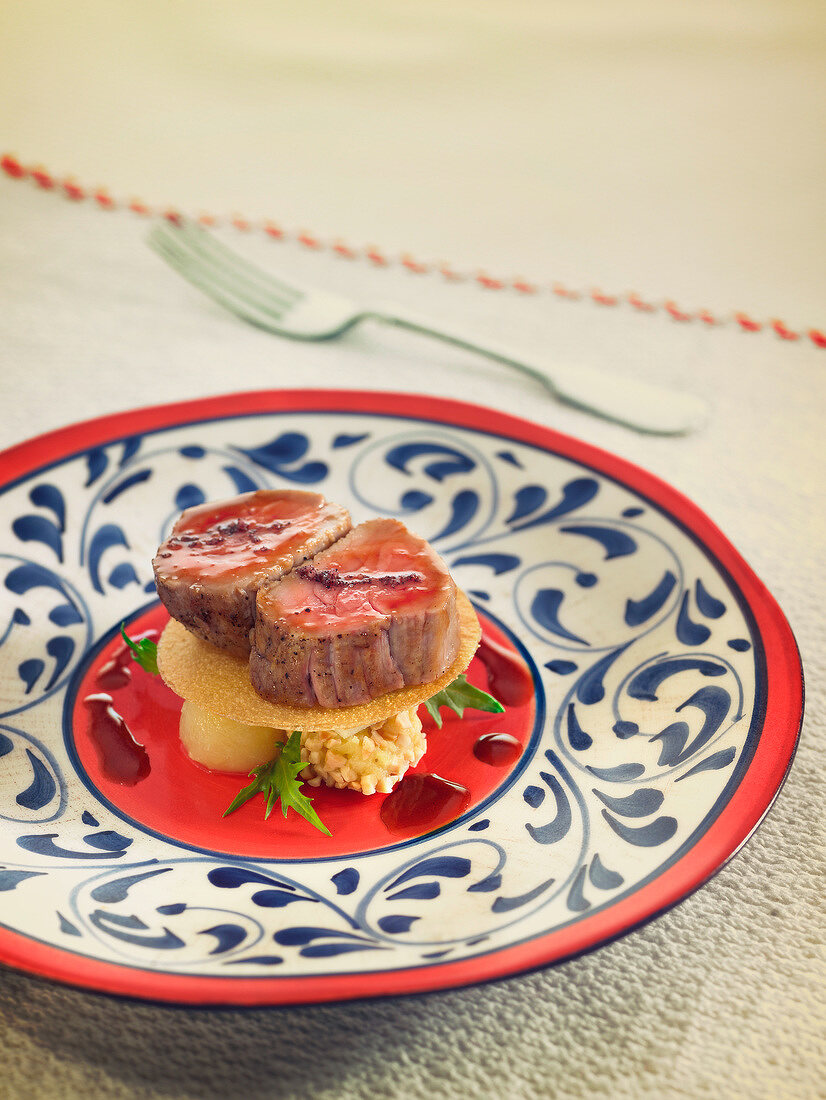 Spanish-style pork fillet on a crisp tuile and pear and apple balls, sherry sauce