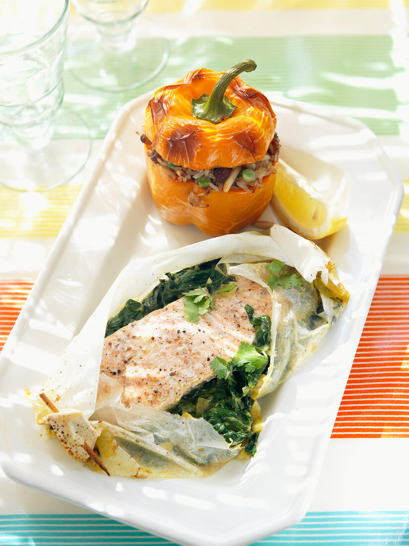 Fish and spinach cooke in wax paper and a stuffed yellow bell pepper