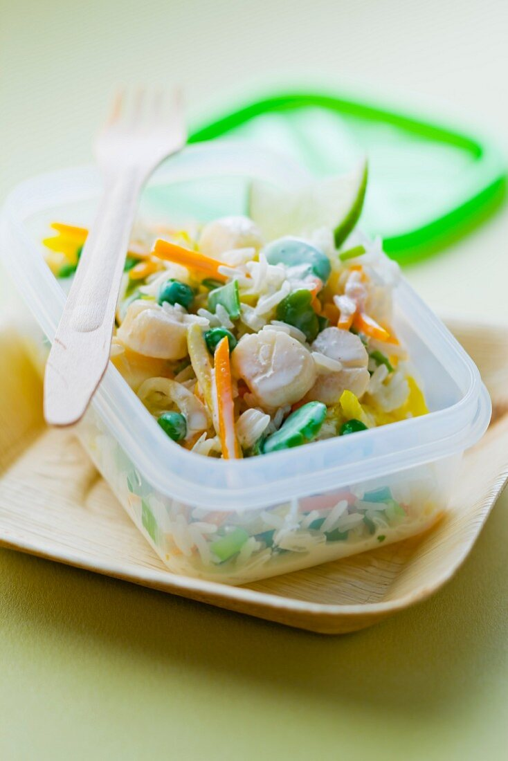 Rice salad with scallops in a take-away plastic container