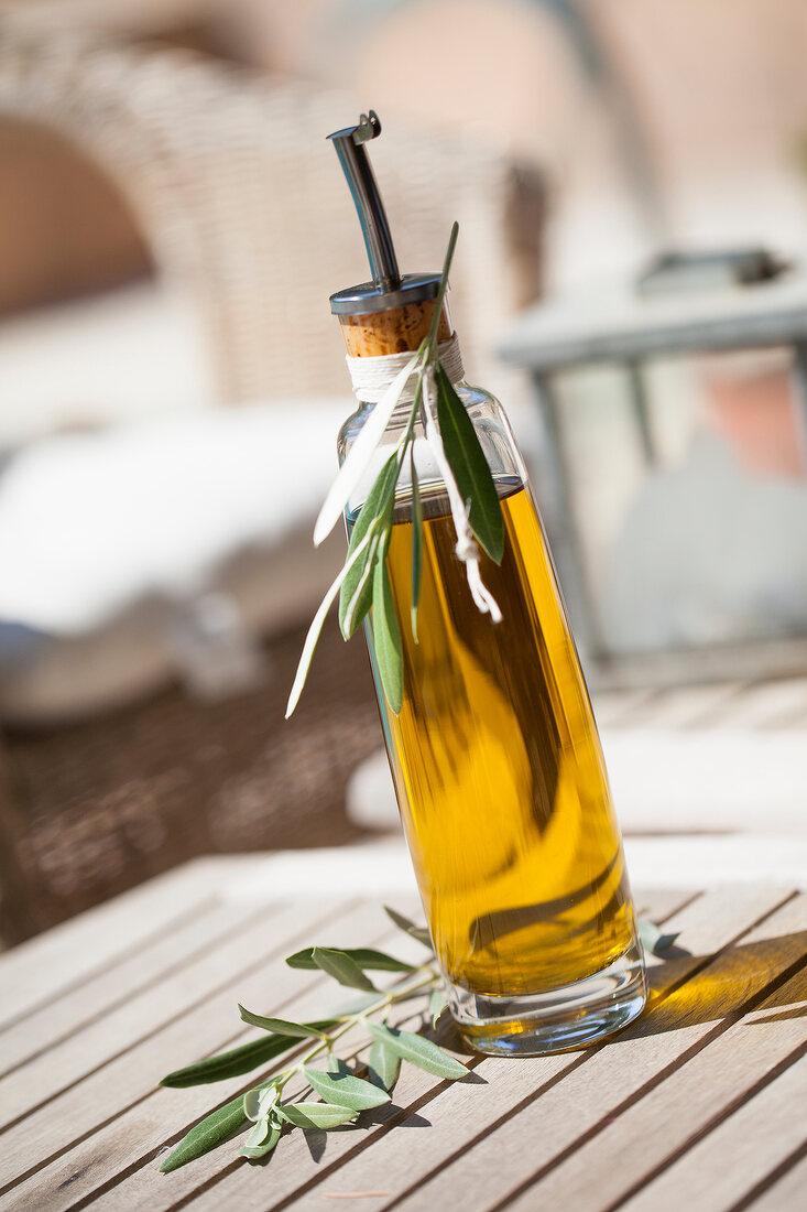 Flasche Olivenöl auf Holztisch im Freien