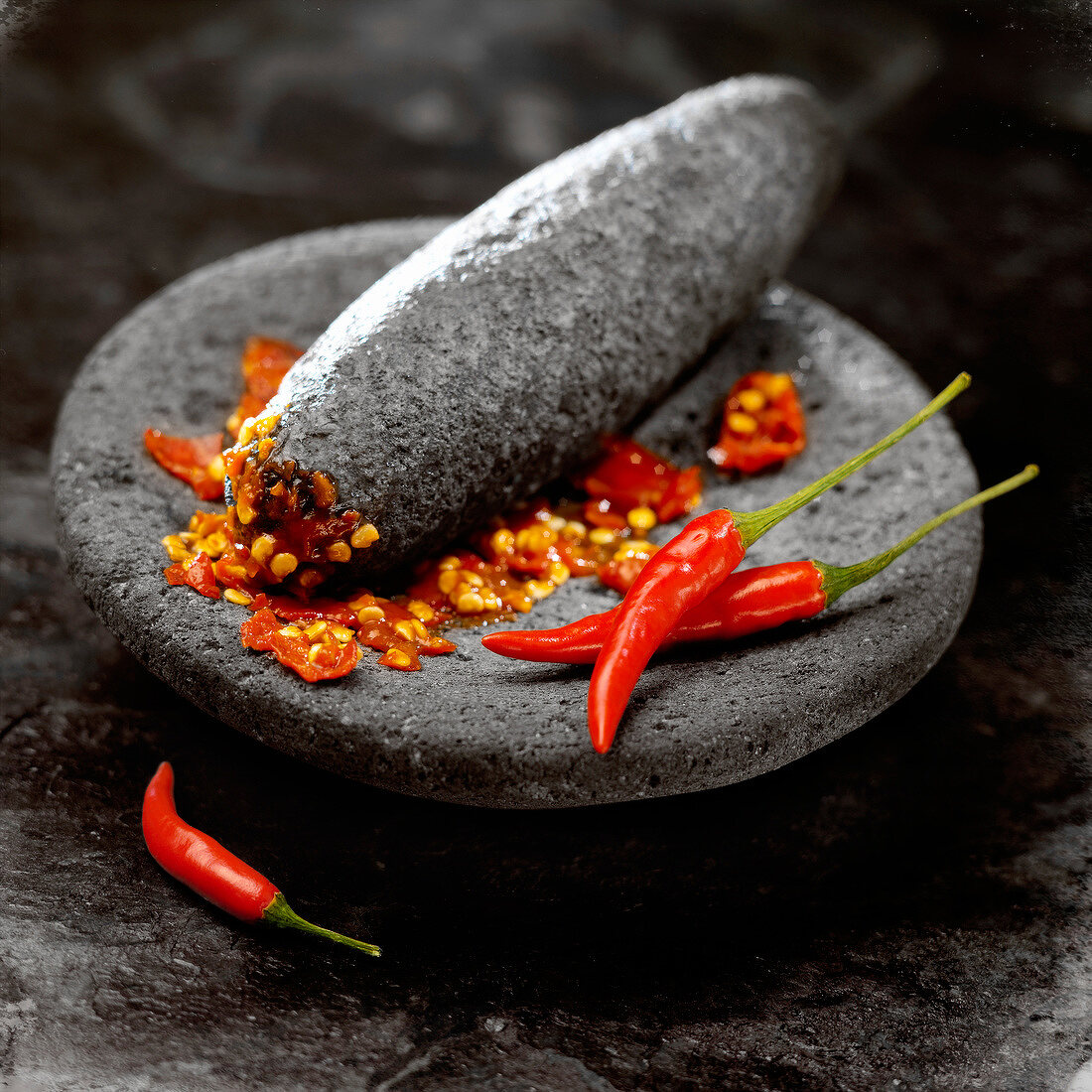 Crushed red peppers in a black volcanic rock mortar