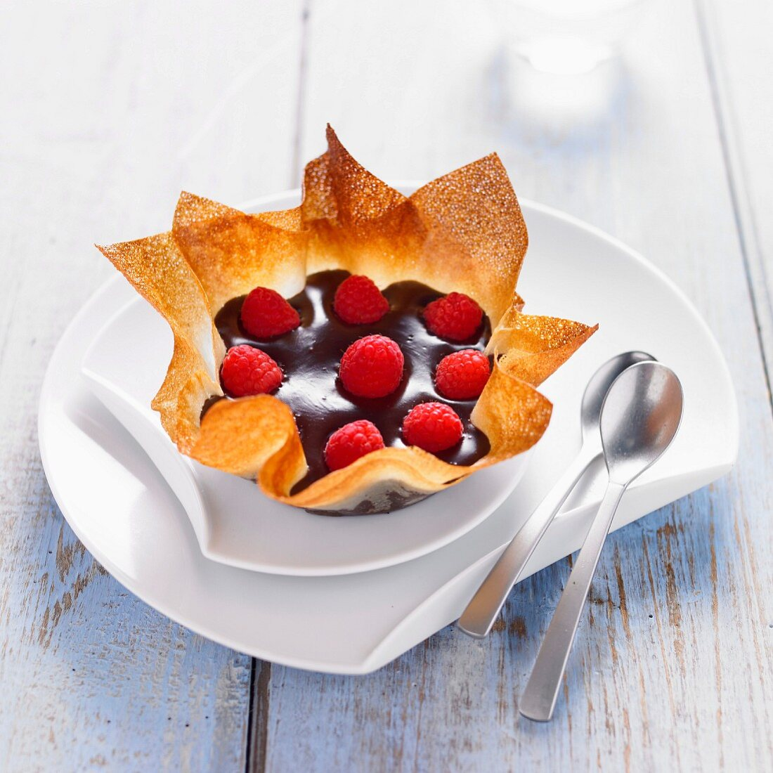 Dark chocolate cream and raspberries in a thin flower-shaped pastry casing