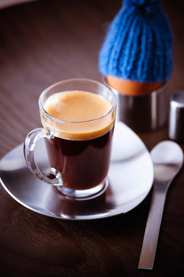 Cup of expresso coffee and a soft-boiled egg with a woolly hat