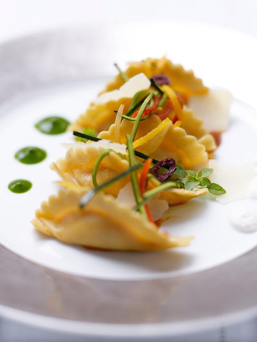 Fresh raviolis with basil pesto and parmesan flakes