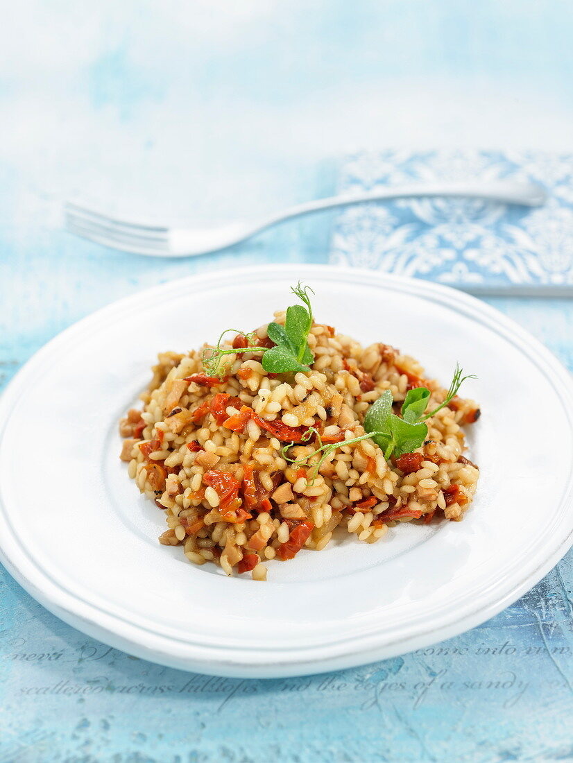 Round rice cooked in chicken stock with smoked chicken and tomatoes