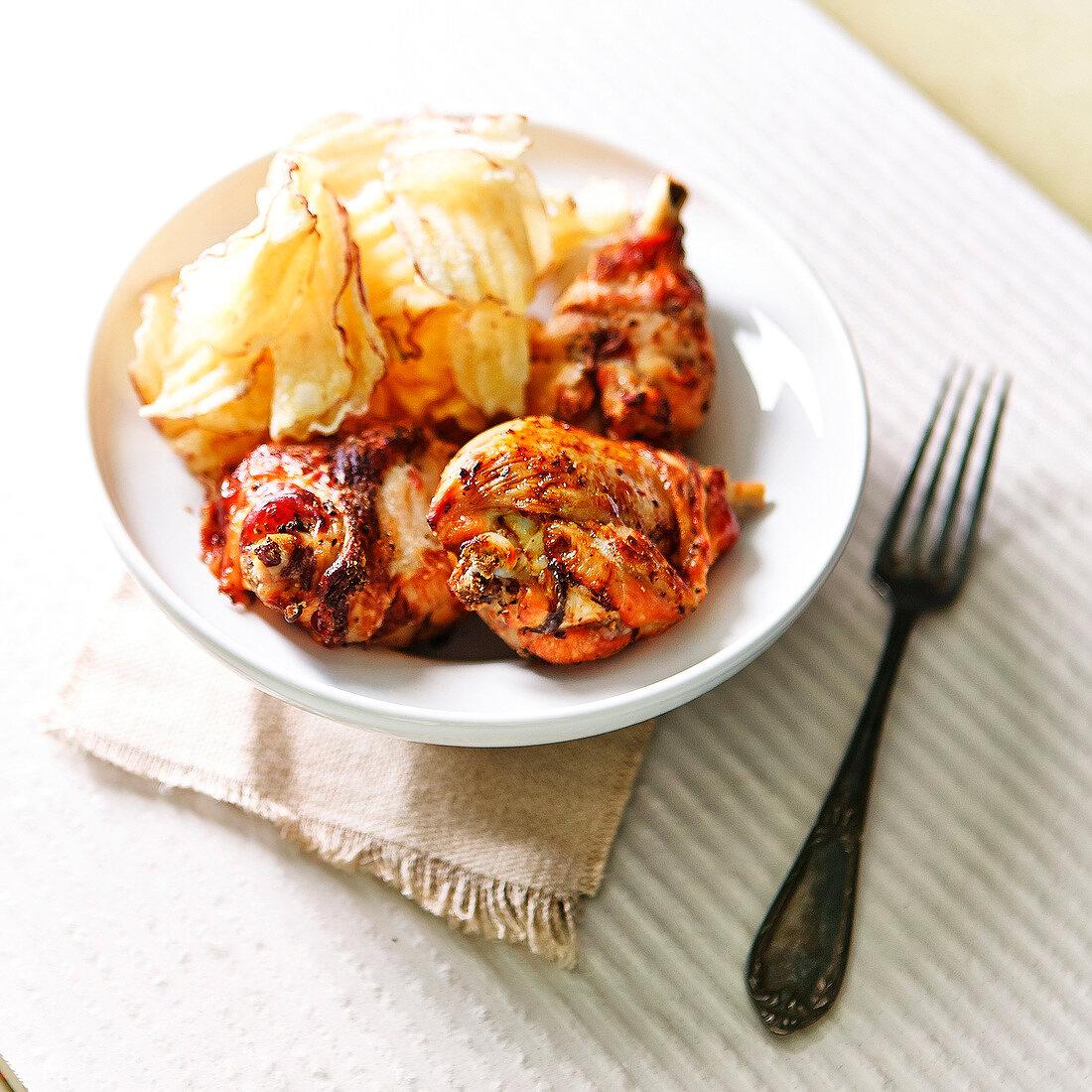 Curried chicken drumsticks and potato crisps