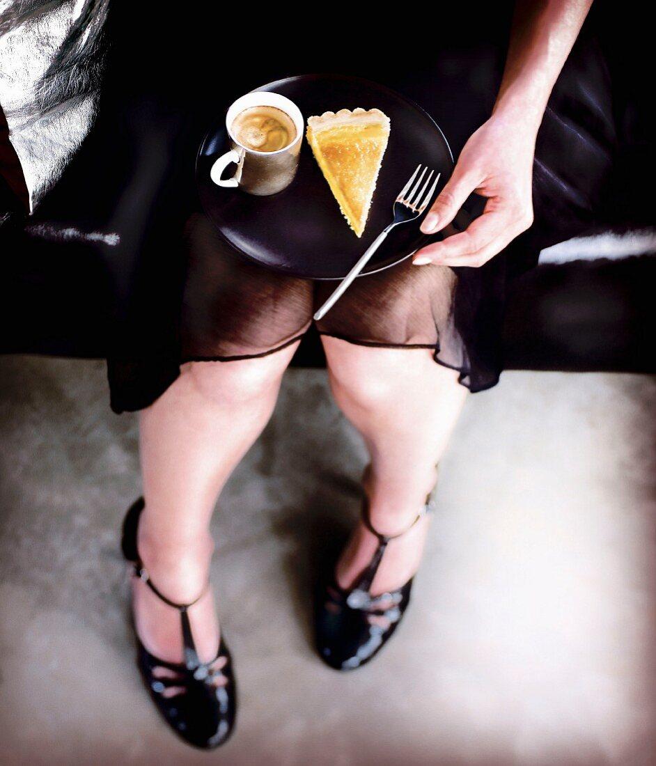 Frau in Abendkleid hält Teller mit einem Stück Orangentarte und einer Tasse Kaffee auf den Knien