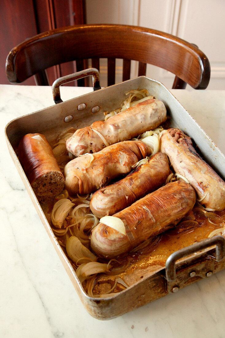 Andouillettes (französische Würstchen) mit Zwiebeln in Bratform