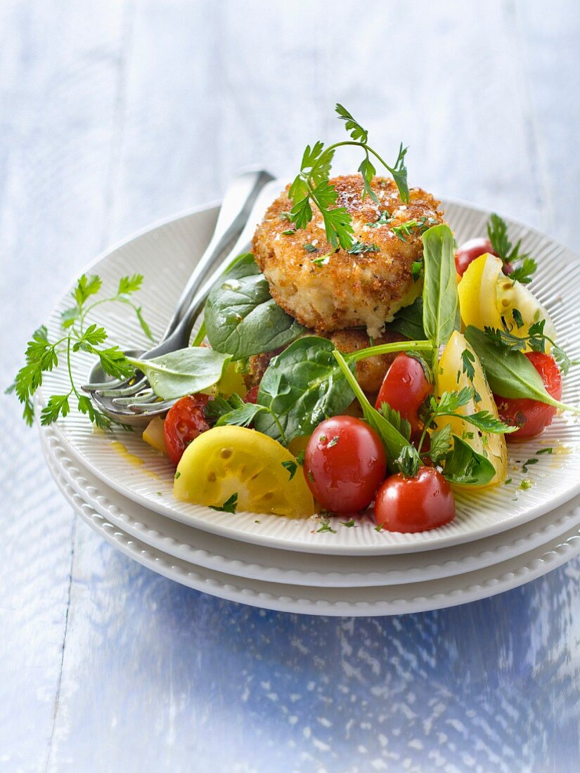 Red and yellow cherry tomato and baby spinach salad with fish cake