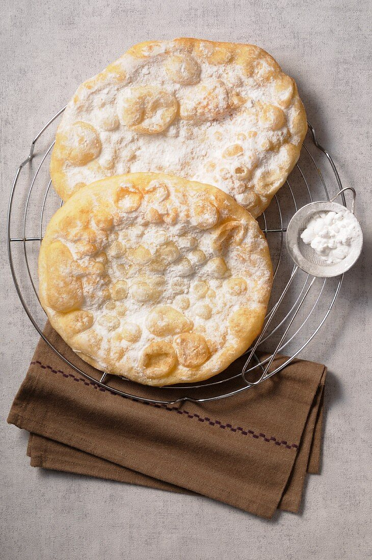 Fried galettes sprinkled with icing sugar