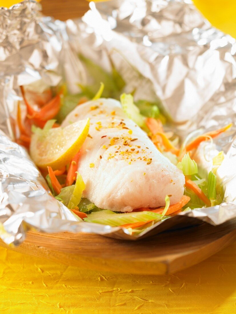 Piece of hake with spices,fennel and lemon cooked in aluminium foil