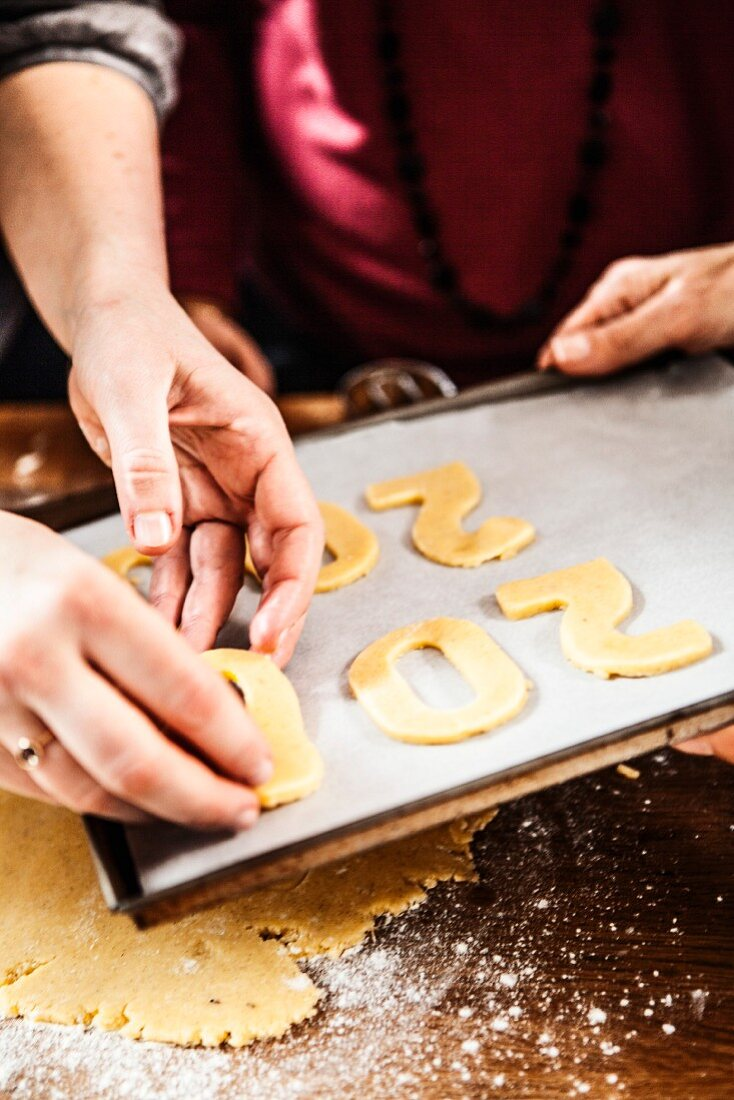 Placing the number-shaped cookies onto a baking tray