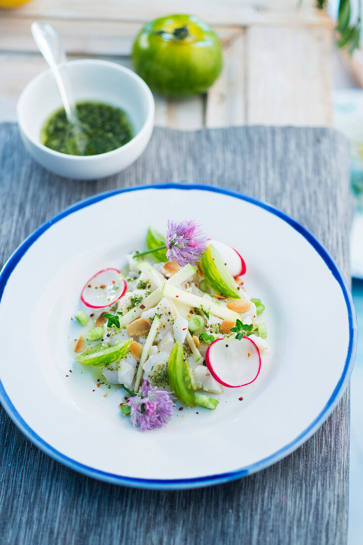 Cod tartare with radishes,green apple and tomato,edible flowers and virgin sauce