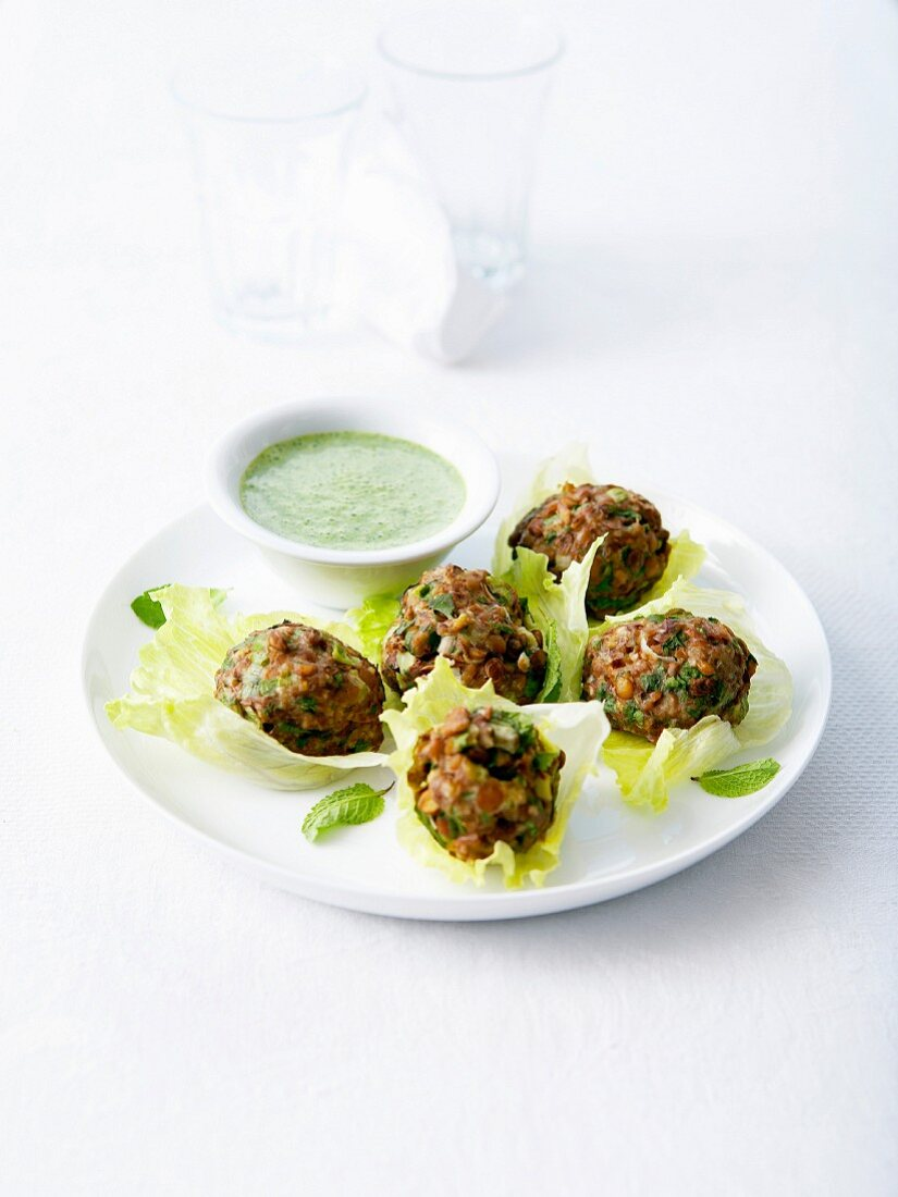Lentil balls served in lettuce leaves with creamy mint sauce