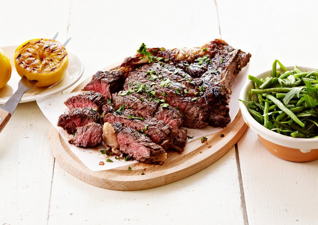Grilled beef chop with mixed green bean and rocket lettuce salad
