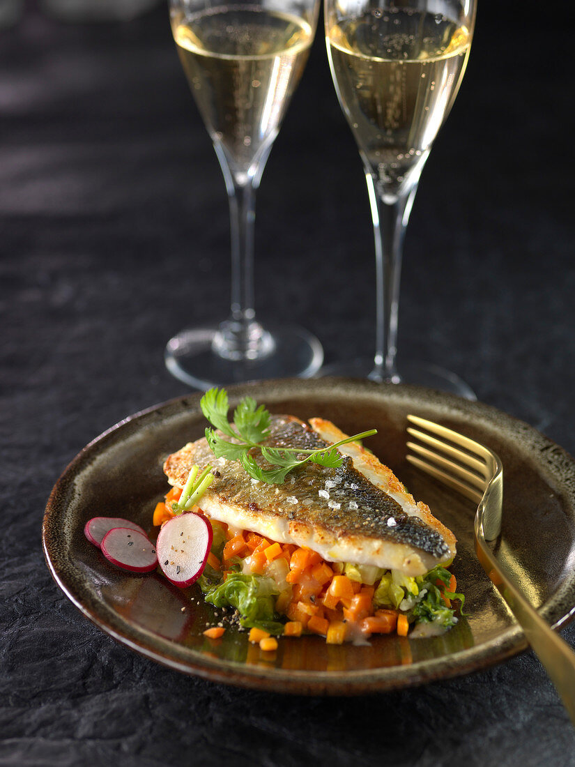 Roasted sea bream on a bed of diced vegetables in reduced Champagne sauce