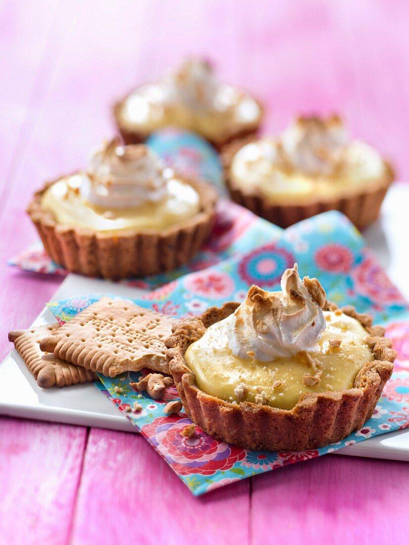 Lemon meringue pies sprinkled with tea biscuit crumbs
