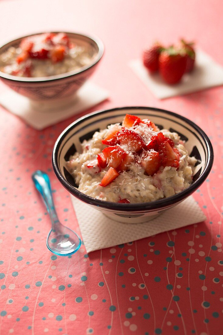 Coconut milk porridge with strawberries and grated coconut