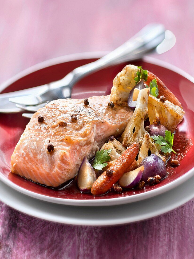 Piece of salmon cooked on one side with coffee and Sechuan pepper, sauteed vegetables