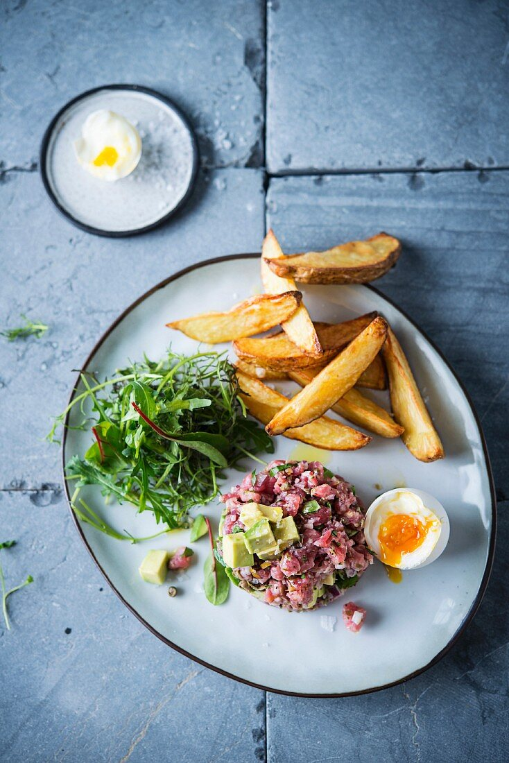 Beef tatar with avocado, a soft-boiled egg and chips