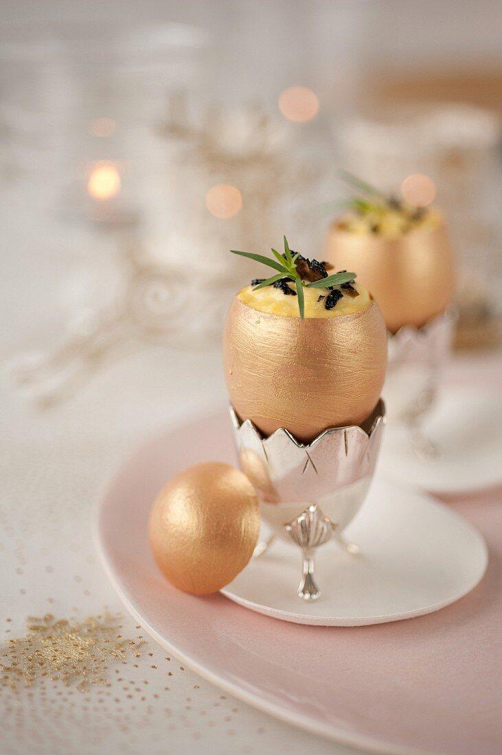 Scrambled eggs with trufles in golden eggshells