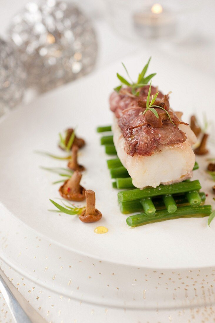 Small roasted monkfish fillet coated with thinly sliced duck breasts,green beans with butter,chanterelles with tarragon